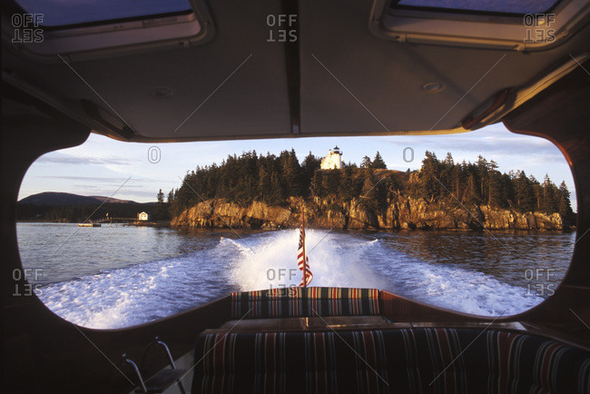 Picnic boat travels near a lighthouse in Maine