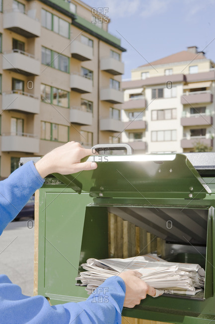 Person throwing newspapers into a recycling bin