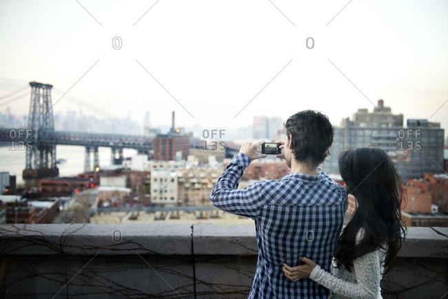 A couple photographs the Brooklyn Bridge
