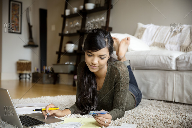 A young woman paying bills online