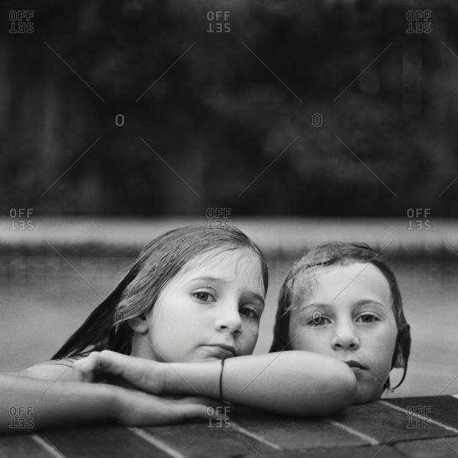 A boy and girl peer out of a pool