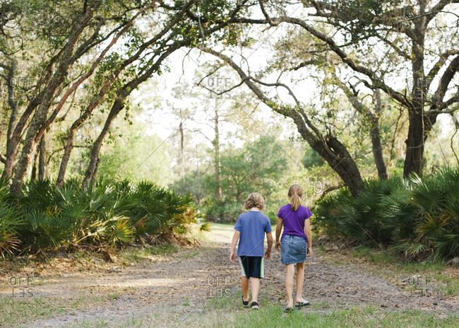 A boy and girl walk down a path