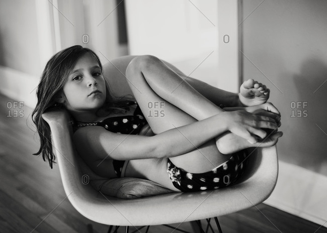 A girl curls up in a chair