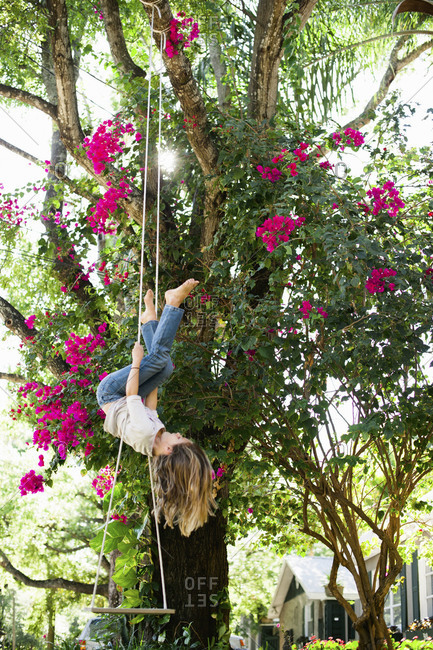 A girl hangs upside-down from a swing