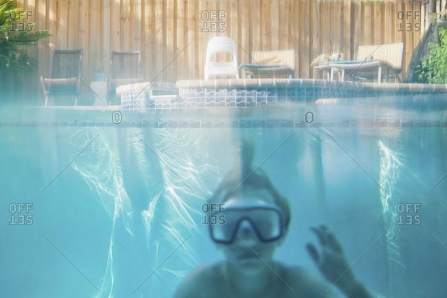 A boy in a swim mask submerged in a pool
