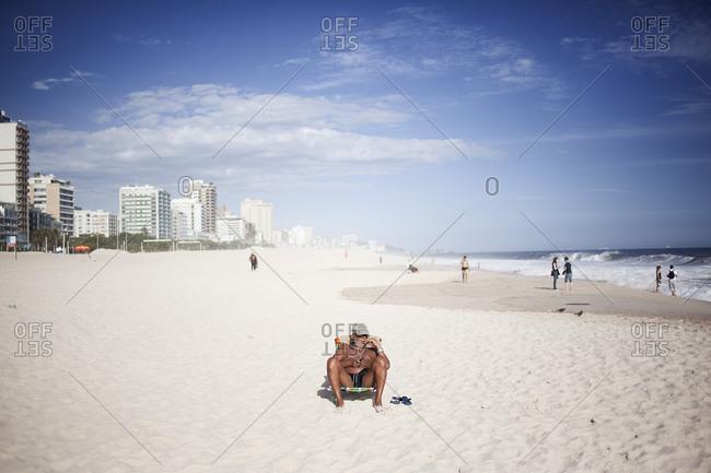 Rio de Janeiro, Brazil - November 30, 2012: A man suns himself at Ipanema Beach in Rio de Janeiro