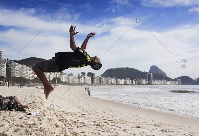 Rio de Janeiro, Brazil - October 30, 2012: A man doing a back flip at Copacabana Beach in Rio de Janeiro