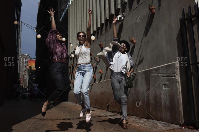 Johannesburg, South Africa - November 27, 2012: Three women jumping on a street in Johannesburg, South Africa