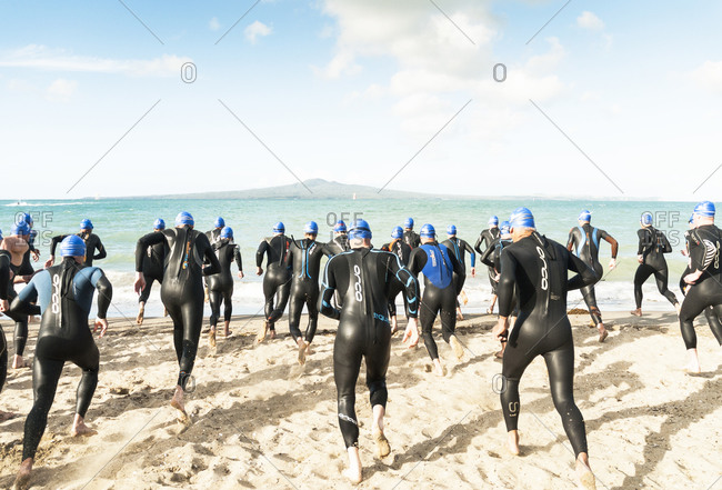 Auckland, New Zealand - January 17, 2013: Triathletes running into the sea at the start of their race in Auckland New Zealand