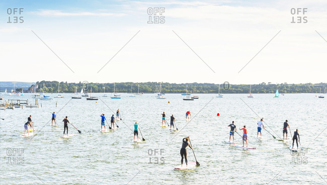 Poole Harbor, Poole Dorset UK - July 16, 2014: A group of people paddle boarding in Poole Harbor