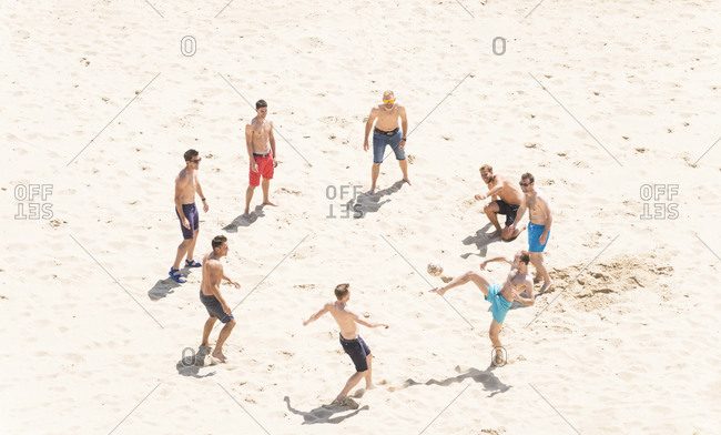 Bournemouth, Dorset, UK - August 19, 2013: A group of young men playing with a soccer ball on the beach