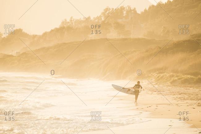 Tarifa, Spain - April 18, 2013: Man carrying a windsurfer along the beach