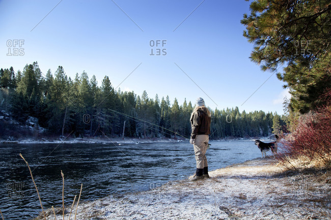 A woman fishing with her dog