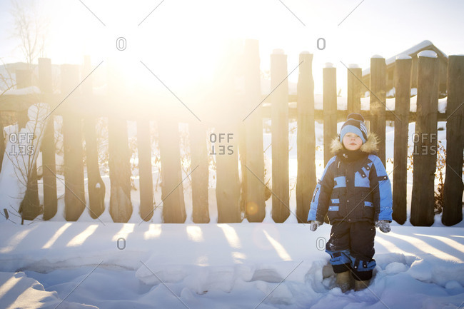 Young boy standing in snow by fence