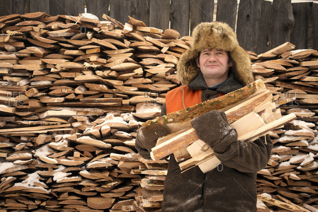 Man holding chopped wood in front of wood pile