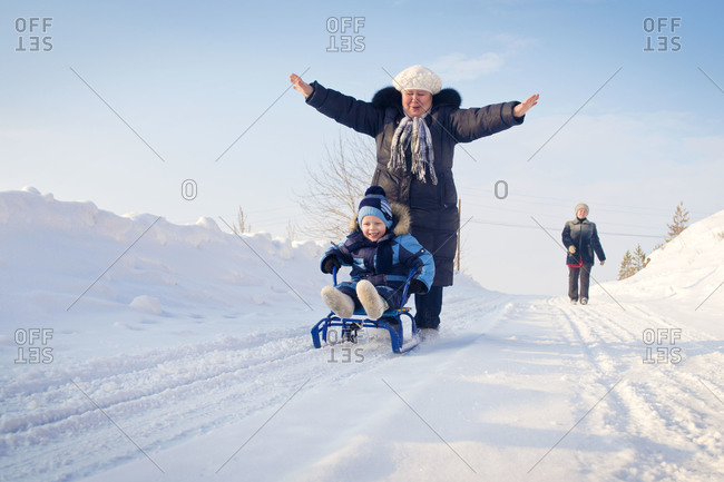 Family sledding down a snow covered hill