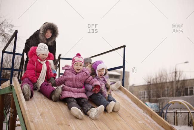 Little girls going down slide in winter