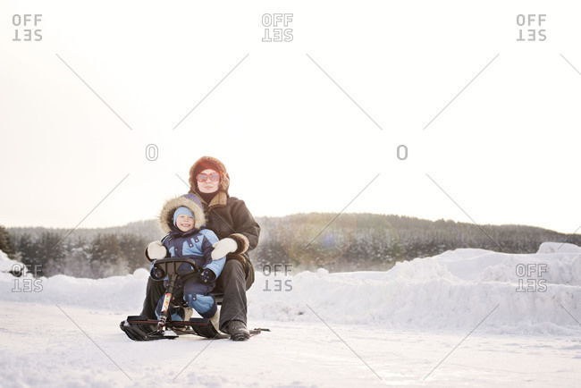 Mom and son sitting on mini snowmobile