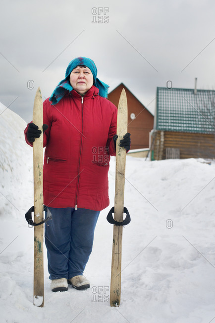 Woman  carrying wooden skis in snow