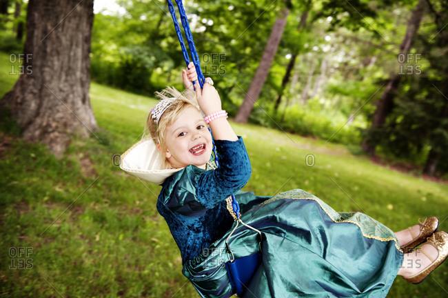 Girl in princess dress on swing