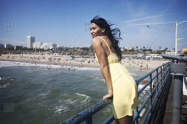 Woman leaning off an ocean pier near a crowded beach