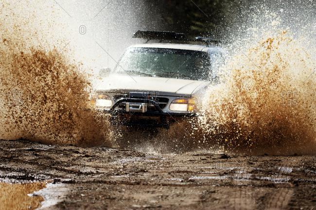Mud bogging truck riding through deep mud