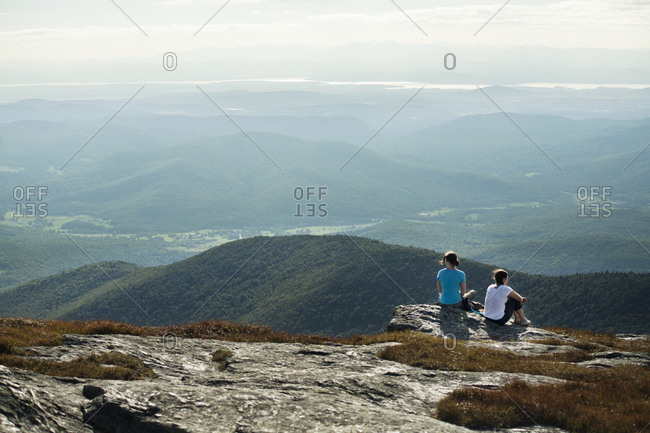 Two hikers sitting on a mountain edge
