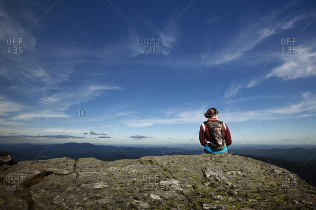 Woman sitting on edge of mountain looking at view
