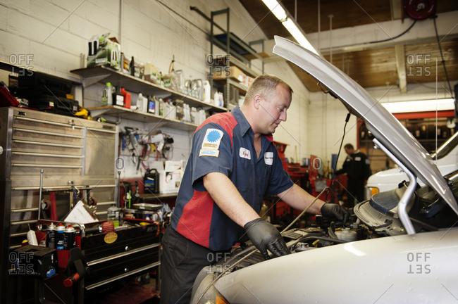 A mechanic looks under the hood of a car