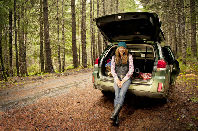 A woman leans against her car
