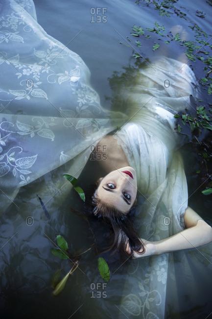 A woman lays in dark murky water