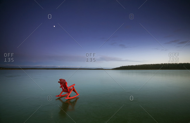 Red rocking chair on a frozen lake