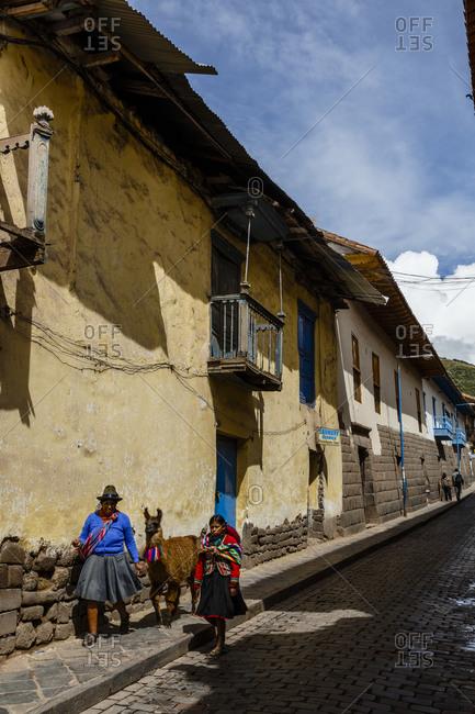 Cuzco, Peru - January 5, 2013: Women with traditional dress along Tupacos wall on San Agustin street in Cuzco, Peru