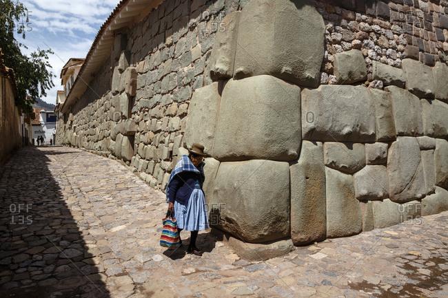 Cuzco, Peru - January 5, 2013: A woman with traditional costume walking along the Inca wall at Hathunrumiyoq Street in Cuzco, Peru
