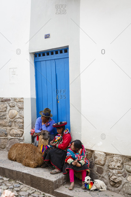 Cuzco, Peru - January 5, 2013: Quechua women with a llama and a lamb in the San Blas neighborhood, Cuzco, Peru.