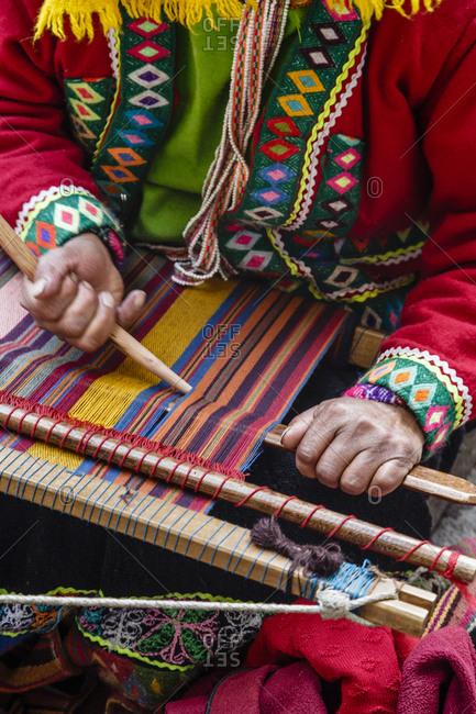 A quechua women weaving a traditional textile in Cuzco, Peru