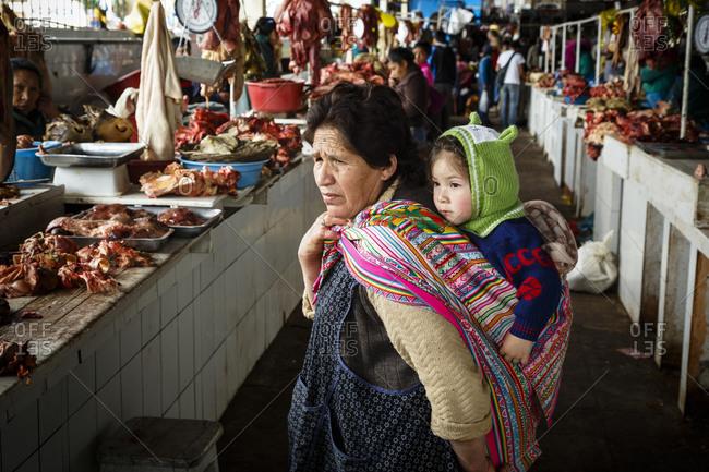 Cuzco, Peru - January 7, 2013: A woman and a baby at San Pedro Market in Cuzco, Peru