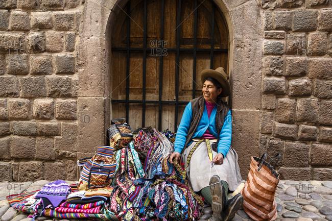 Cuzco, Peru - January 7, 2013: A quechua woman selling belts and carpets on Loreto street in Cuzco, Peru