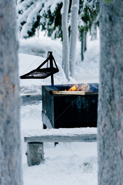 A fire burring in a lean-to in the snowy Swedish landscape