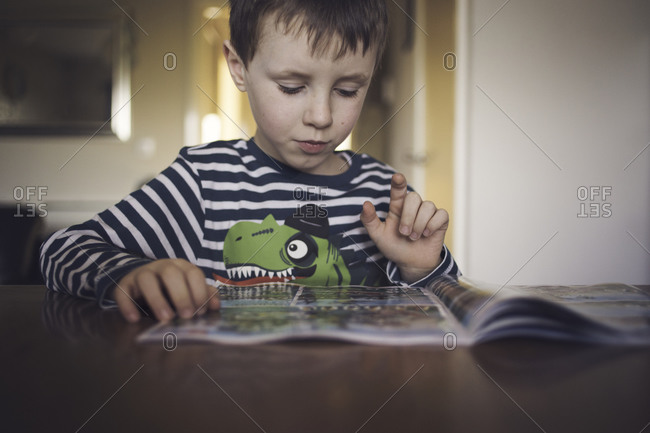 A boy reads a comic book
