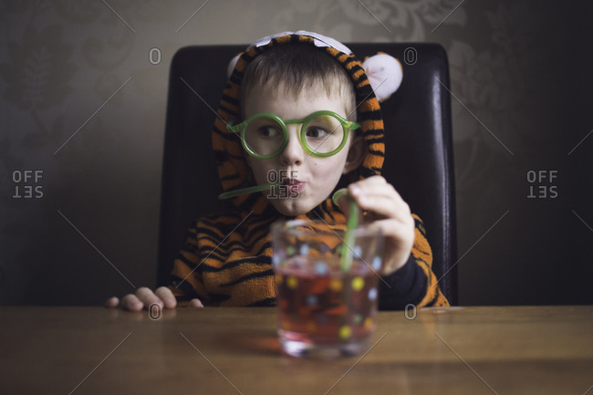 A boy in a tiger suit wearing drinking straw glasses