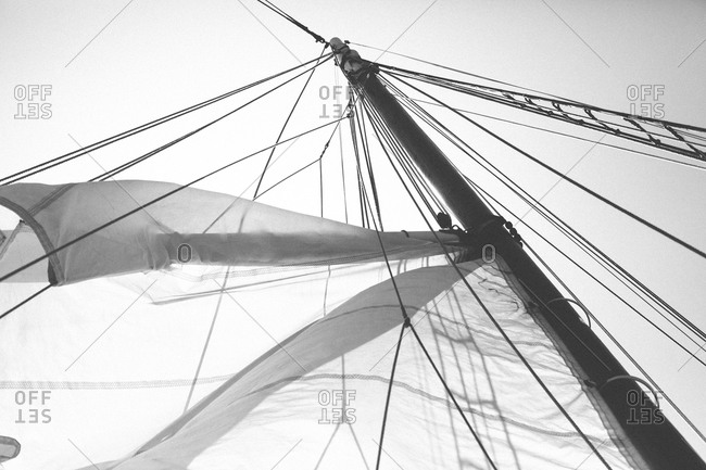 Lines and sail extending from a sailboat mast