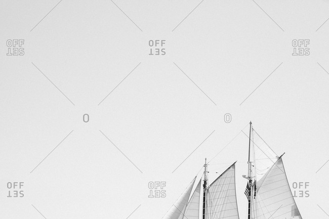 Sails of a schooner in an empty sky