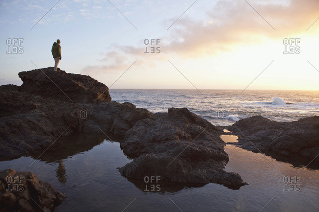 Man looking at the ocean from coastal rocks