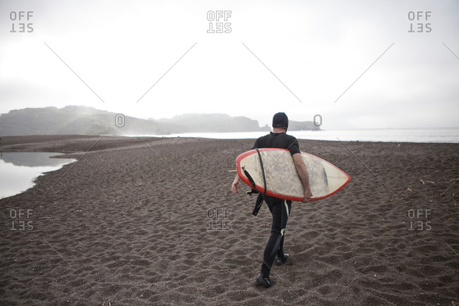 A surfer carrying his board to the water