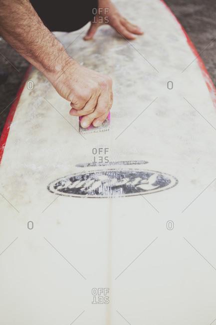Man's hands applying wax to a surfboard