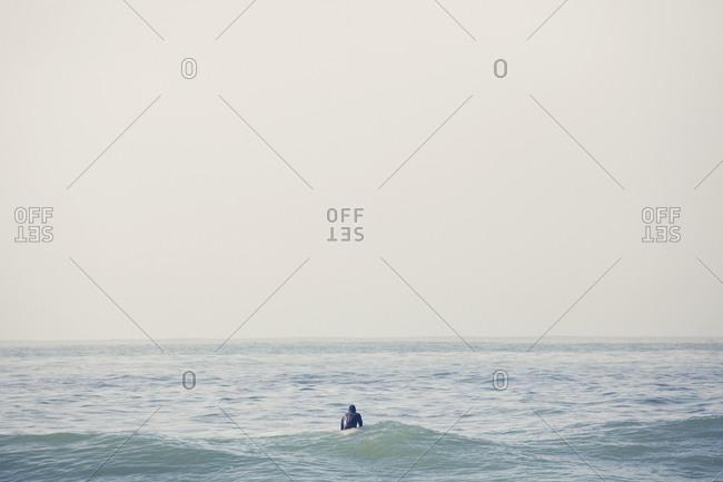 Surfer sitting on surfboard in mostly flat seas