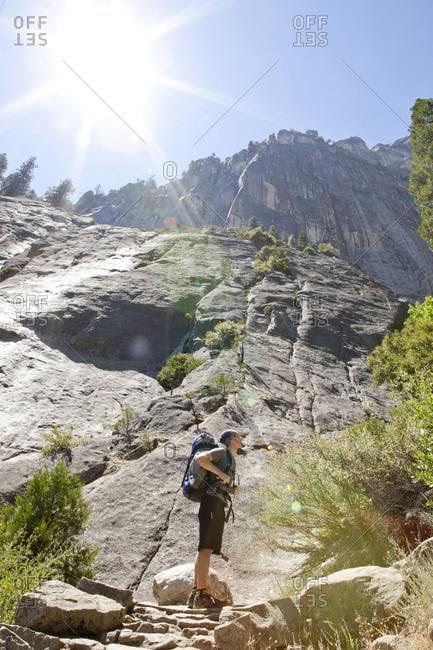 Hiker gazes upwards at rock formations