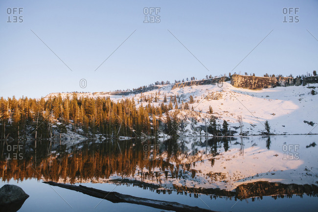 Snow-covered hill reflected in a lake in afternoon light