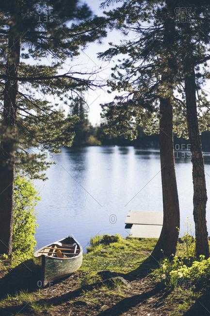 Canoe resting on the lakeshore near dock